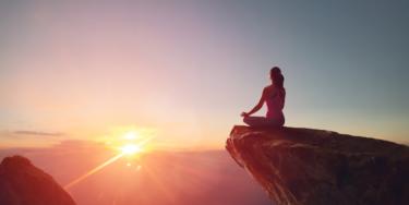 山で夕陽を見ている女性の画像