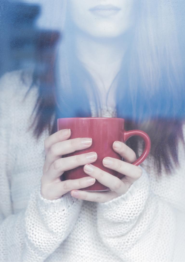 窓辺に女性がマグカップを持っている画像