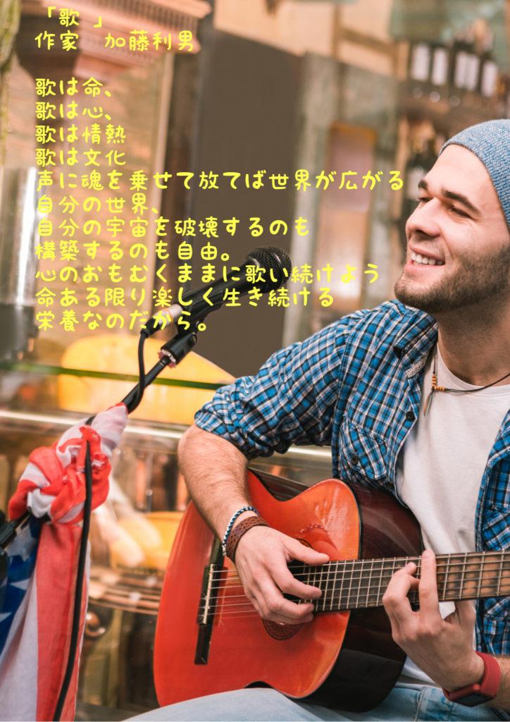 ギターを弾きながら歌っている男性の画像