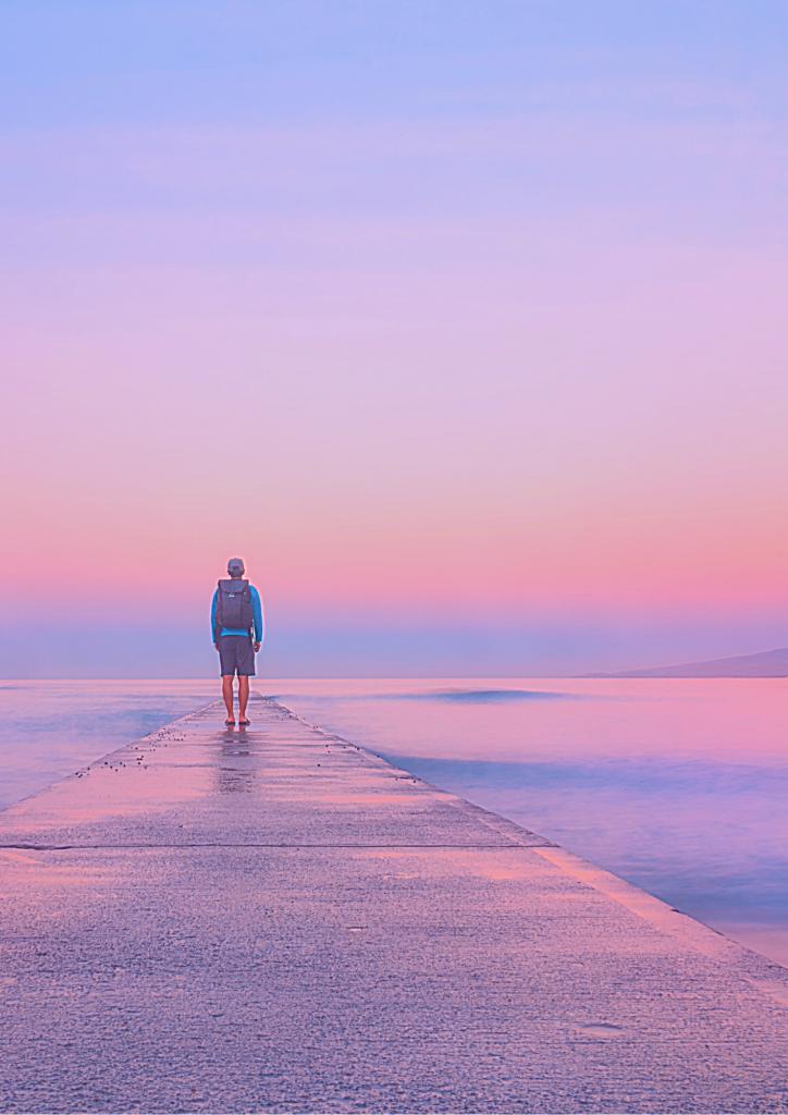 海を眺めている男性の後ろ姿の画像