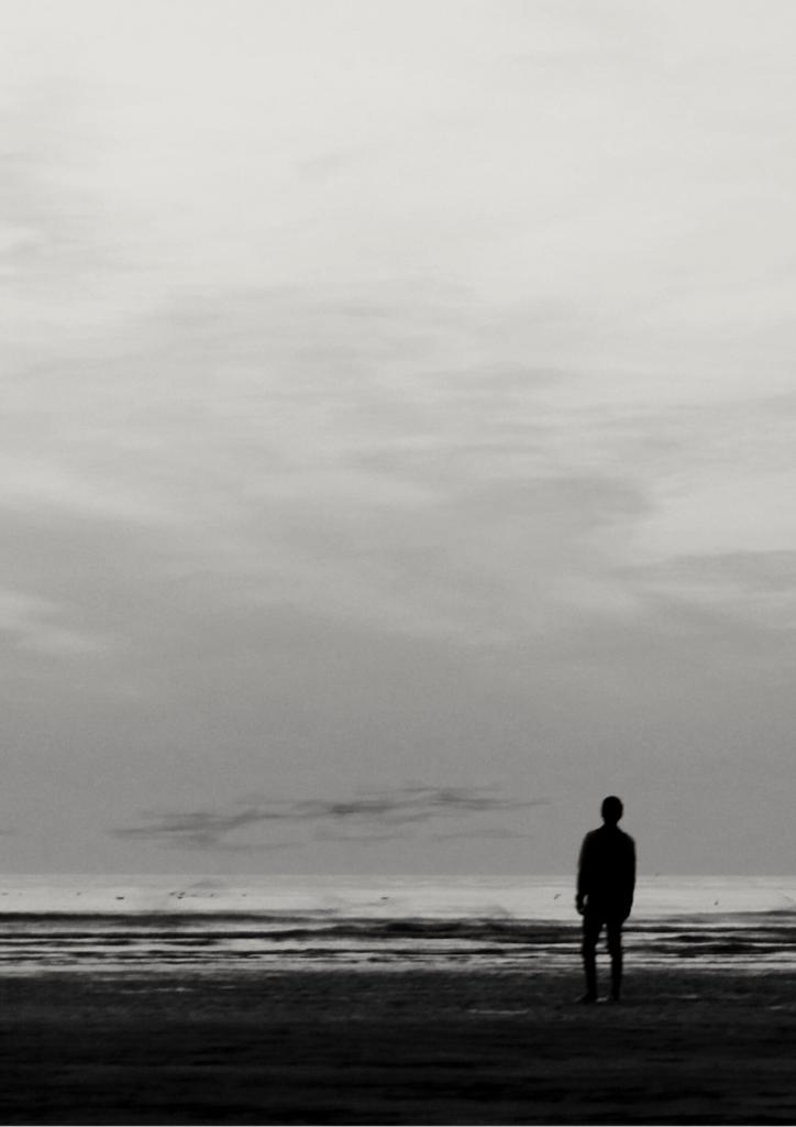 水辺に佇む男性の画像