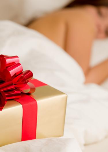 ベッドに寝ている女性とプレゼントの画像