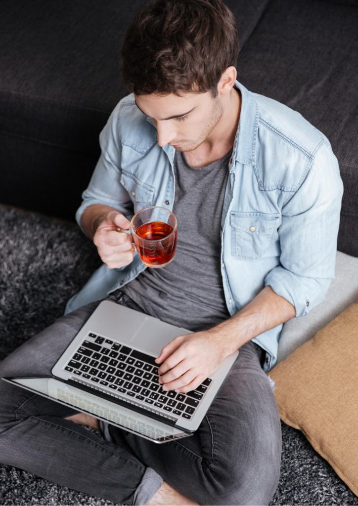 紅茶を飲みながらパソコンを触る男性の画像
