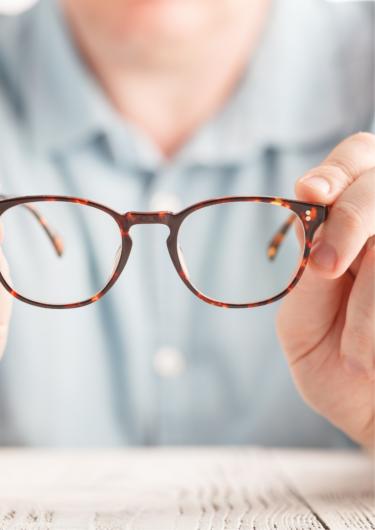 メガネを持っている男性の画像
