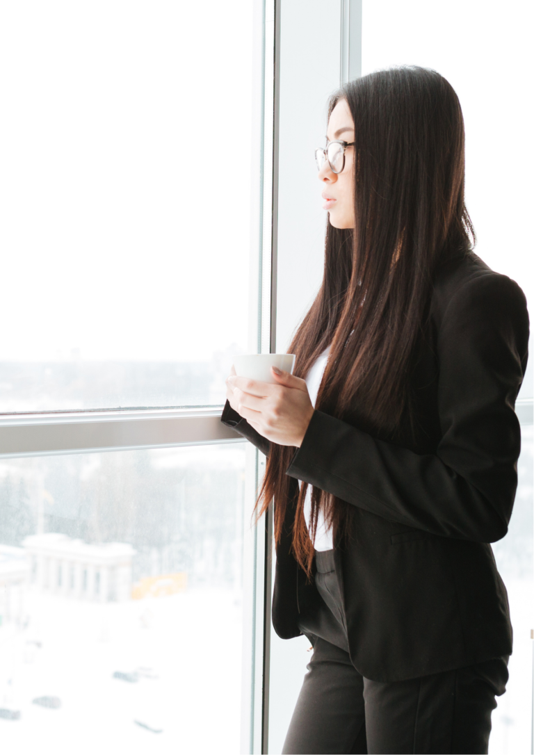 オフィスで窓を眺めている女性の画像
