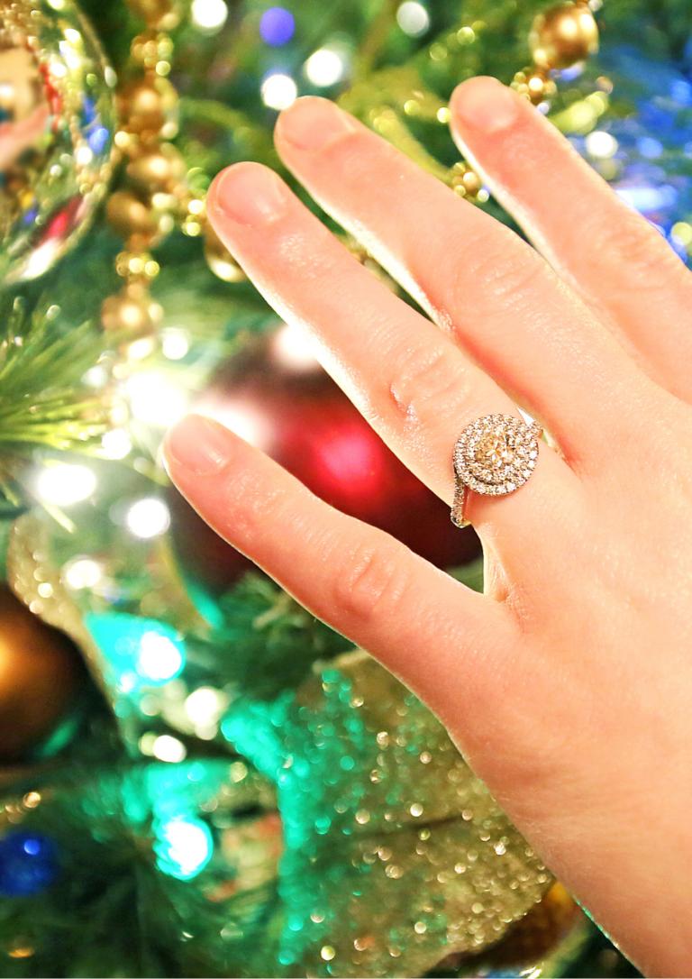クリスマスツリーと指輪をしている手の画像