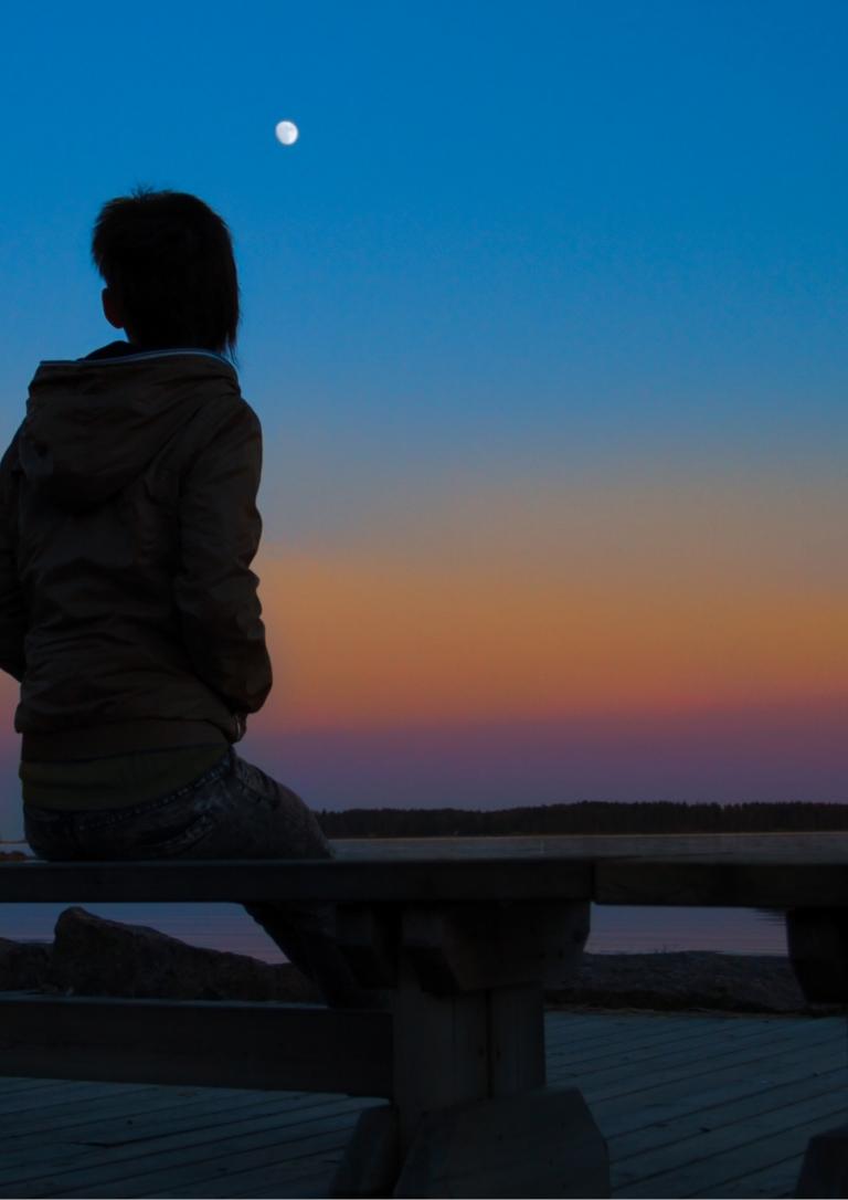 夕暮れの海を眺める人の画像